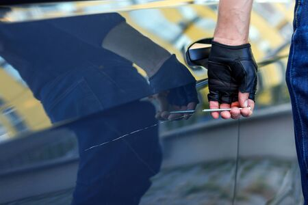 Closeup bully hands in black gloves are scratching automobile with nail, pin. Bandit is spoiling appearance of private car. Man is making scratch on auto without signaling. Vandalism act concept. Stock fotó