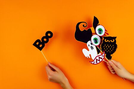 Female hands are holding paper photo props on orange background. Scary ghost, owl, vampire smile, teeth, blood eyes, witch hat on canvas. Party carnival, accessories for celebrating happy halloween. Banco de Imagens