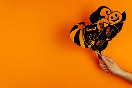 Female hand is holding funny paper photo props on orange background. Black cat mask, owl, pumpkin glasses, witch hat on canvas. Party carnival, accessories for celebrating happy halloween.
