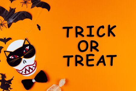 Visage drôle de monstre crâne avec masque de chat, cravate papillon. Fournitures de carnaval sur le côté gauche de la toile. Accessoires de fête sur fond avec des araignées et des chauves-souris. Truc ou friandise d'inscription. Joyeux Halloween.