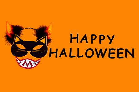 Funny face of cat monster with vampire smile, headwear horns on orange background. Paper decor, photo props with black inscription happy halloween on canvas. Party accessories for celebration. Фото со стока