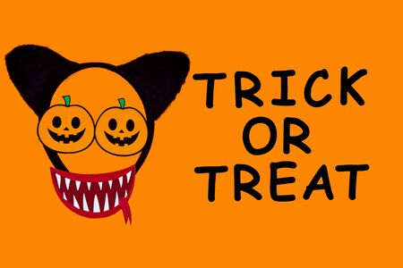 Funny face of monster made of photo props with headwear ears of cat. Carnival decor in left side of canvas. Party accessories on orange background. Black inscription trick or treat. Happy halloween.