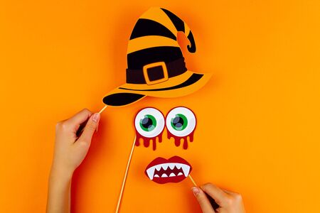 Funny face of monster with witch hat, blood eyes and vampire smile on orange background. Female hands are holding paper photo props on canvas. Party accessories for celebration happy halloween. Фото со стока - 131415502