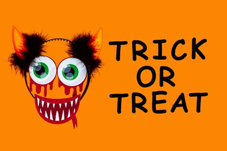 Funny face of monster made of paper photo props with headwear horns. Carnival decor in left side of canvas. Party accessories on orange background. Black inscription trick or treat. Happy halloween.