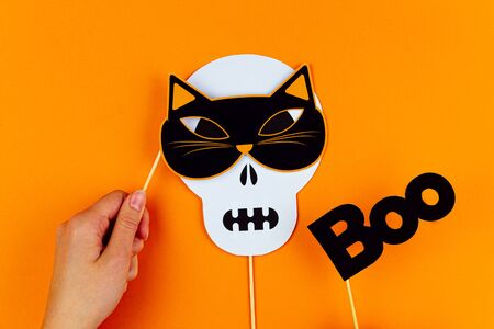 Funny face of skull monster with cat mask and black inscription boo on orange background. Female hand is holding paper photo props on canvas. Party accessories for celebrating happy halloween. Фото со стока