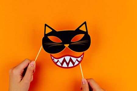 Funny face of monster with cat mask and vampire smile on orange background. Female hands are holding paper photo props on canvas. Party carnival accessories for celebration happy halloween.