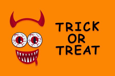 Funny face of monster with horns, vampire smile, blood eyes on orange background. Paper decor, photo props with inscription trick or treat on canvas. Party accessories for celebration happy halloween.