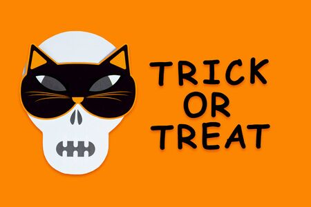Funny face of skull monster with cat mask. Carnival supplies, decor with black inscription trick or treat on orange canvas. Party accessories, photo props on background. Greeting card happy halloween.