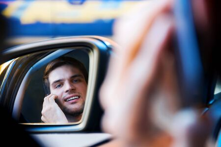Portrait of driver in car rear view window. Businessman is talking on smartphone behind steering wheel of auto. Young man is not attentively driving automobile. Guy is breaking rules of road. Фото со стока - 131487541