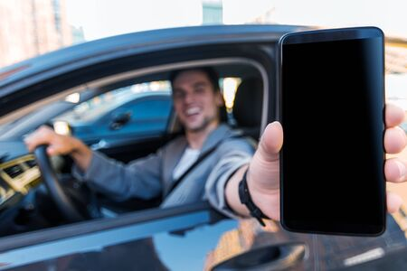Closeup male hand is holding smartphone with blank screen. Smiling businessman in grey suit behind steering wheel of car. Man is driving automobile. Application, software for drivers concept.