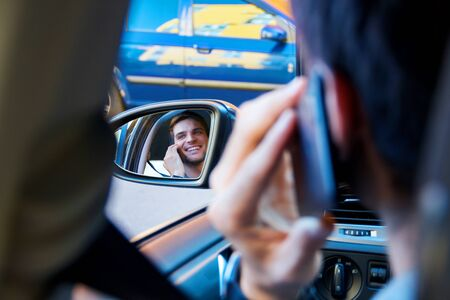 Portrait of driver in car rear view window. Businessman is talking on smartphone behind steering wheel of auto. Young man is not attentively driving automobile. Guy is breaking rules of road.