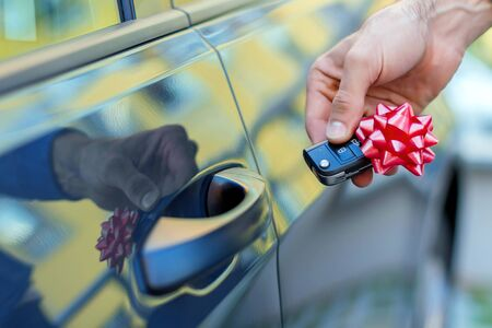 Closeup male hand of new black car is holding gift, surprise, keys with red bow. Lucky driver is going to sitting behind steering wheel of automobile. Man winner won auto in raffle, lottery. Фото со стока