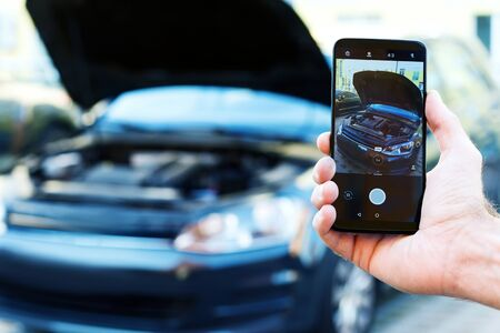 Closeup male hand is holding smartphone with picture of auto with open hood. Mechanic repairman is making photo of automobile engine motor. Software for car diagnostics and maintenance concept.