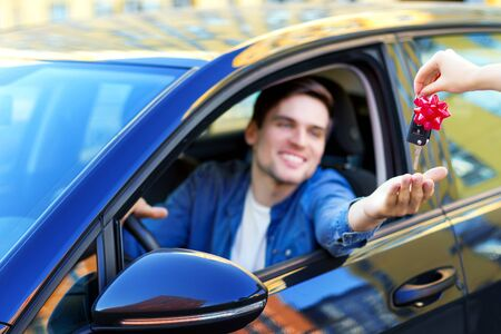 Happy smiling owner of new black car is taking from seller keys with red bow. Driver in denim shirt is sitting behind steering wheel of automobile. Joyful man brunette bought auto at dealership.