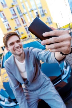 Closeup male hand is holding smartphone. Happy brunette man owner is making selfie with new car. Black automobile on parking on background. Smiling businessman in grey suit bought auto.