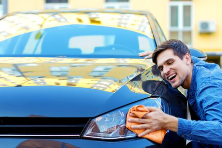 Happy cheerful owner of new black car is wiping, cleaning auto with orange rag. Smiling brunette man driver in denim shirt is hugging and stroking vehicle. In love with automobile concept.