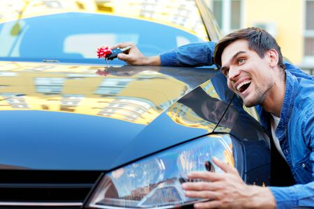 Happy cheerful owner of new black car is holding gift, surprise, keys with red bow. Smiling brunette driver in denim shirt is hugging and stroking automobile. Man winner won auto in raffle. Stock fotó