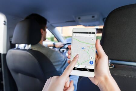 Closeup female hand is holding smartphone with online map on screen, shows way to home. Woman is riding on back seat of automobile car. Taxi booking application, mobile GPS navigator concept.
