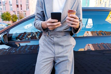 Closeup male hands are holding smartphone and coffee. Businessman in grey suit is having break after meeting at car parking. Man driver is standing near automobile on street at modern city.