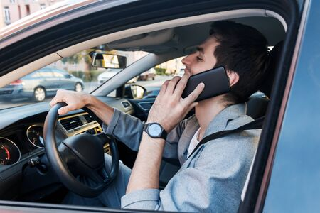 Driver businessman is talking on smartphone behind steering wheel of car. Young man is not attentively driving automobile. Guy is breaking rules of road. Concept of fast rhythm in modern city.