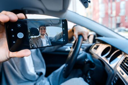 Closeup male hand is holding smartphone with photo on screen. Driver businessman behind steering wheel of car is making selfie and smiling. Man is violating rules of road. Danger on route concept. Фото со стока - 131488114