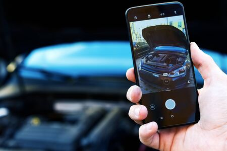 Closeup male hand is holding smartphone with picture of auto with open hood. Mechanic repairman is making photo of automobile engine motor. Software for car diagnostics and maintenance concept. Фото со стока - 131485830