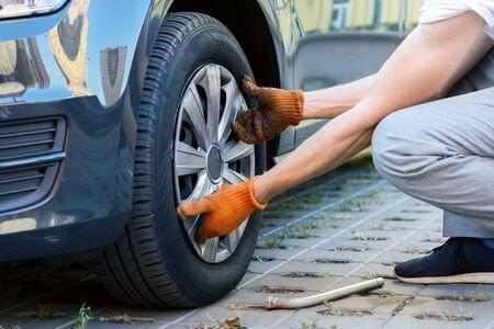 Las manos masculinas del primer en guantes están quitando la rueda del coche. Joven conductor está reparando automóviles en la calle. Avería del vehículo en camino. Mecánico reparador está llevando a cabo el montaje de neumáticos.