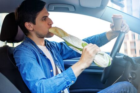 Driver is eating baguette and drinking coffee behind steering wheel of car. Young man is not attentively driving automobile. Guy is breaking rules of road. Concept of fast rhythm in modern city. Stock fotó