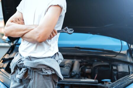 Closeup male hands with metal  wrench for tightening nuts. Car with open hood on background. Young man repairman driver is repairing automobile on street road. Vehicle breakdown on way concept.