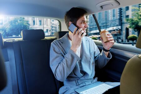 Young brunette man in grey suit is riding in taxi in back seat of automobile. Businessman is talking on smartphone, working on laptop on way to meeting. Concept of fast rhythm of modern city. Фото со стока