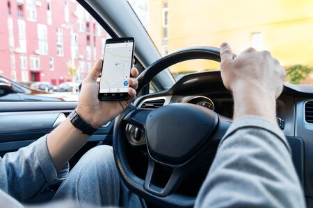 Closeup male hand is holding smartphone with online map on screen, shows way to home. Man  driver is driving, behind steering wheel of automobile car. Mobile GPS navigator application concept. Stock fotó
