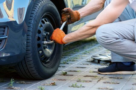Closeup male hands in gloves are removing wheel from car. Young man driver is repairing automobile on street road. Vehicle breakdown on way. Repairman mechanic is carrying out tire fitting.