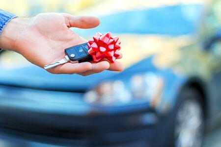 Closeup male hand of new black car is holding gift, surprise, keys with red bow. Lucky driver is going to sitting behind steering wheel of automobile. Man winner won auto in raffle, lottery.