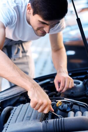 Closeup male hands with metal  wrench are tightening nuts in auto with open hood. Young man driver is repairing automobile on street road. Vehicle breakdown on way. Repairman mechanic is servicing car Фото со стока