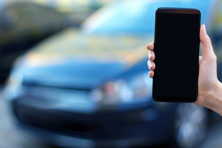 Closeup female hand is holding  smartphone with blank screen display. Black car automobile on street parking on blurred background. Online application, software for using by drivers concept. Stock fotó
