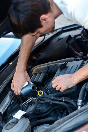 Young brunette man is changing oil in auto with open hood. Driver is repairing automobile on street road. Vehicle breakdown on way concept. Repairman mechanic is servicing car in workshop.