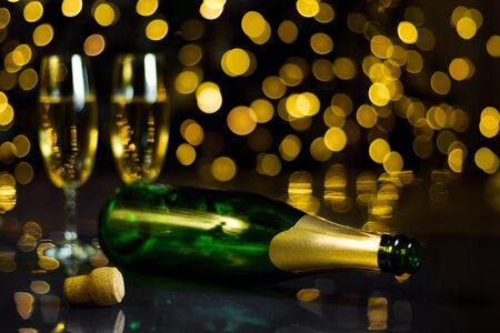 Two glasses with bubbly champagne, empty green bottle are on table. Festive decorative garland with yellow light bulbs are shining on background. New year, christmas mood. Greeting card template.  Stockfoto