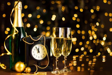 Glasses and bottle with champagne, gold decor, balls, serpentine on table. Clock is showing five minutes to twelve. Garland with yellow light bulbs are shining on background. New year, christmas mood.