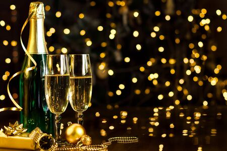 Glasses and green bottle with champagne, gold decor, balls, present, clock, serpentine are on table. Decorative garland, yellow light bulbs are shining on background. New year, christmas mood.