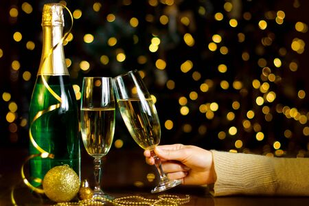 Female hand is clinking glasses with champagne. Gold decor, balls, green bottle are on table. Festive decorative garland with yellow light bulbs are shining on background. New year, christmas mood.