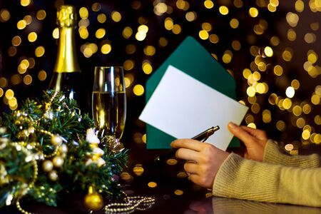 Female hands are holding envelope with blank sheet of paper for greeting card. Decorated wreath, glass with champagne on table. Garland with yellow light bulbs are shining. New year, christmas mood.