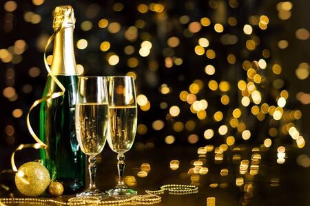 Two glasses and green bottle with champagne, gold decor, balls, serpentine are on table. Festive decorative garland, yellow light bulbs, lanterns are shining on background. New year, christmas mood.