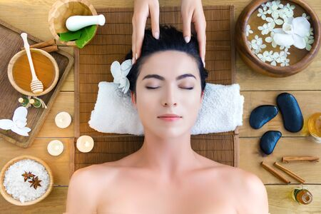 Top view young woman is getting head massage, therapy. Master hands are massaging kneading temples of client. Brunette girl is lying on couch in light spa ayurveda salon. Relax and health care concept Stock Photo