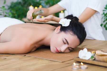 Young pleased woman is getting thai massage, therapy. Female master is pouring massaging oil in palms. Brunette girl is lying on couch in light spa ayurveda salon. Relax and health care concept. Stock Photo