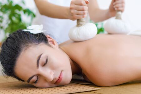 Young pleased woman is getting thai massage, therapy. Female master is massaging client with herbal bags. Brunette girl is lying on couch in light spa ayurveda salon. Relax and health care concept. Stock Photo
