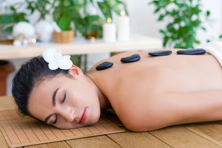 Young pleased woman is getting hot massage, therapy. Basalt black stones are placed along spine of relaxed female. Brunette girl is lying on couch in spa ayurveda salon. Relax and health care concept.