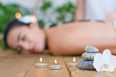 Closeup burning candles, flower, special stones. Young woman is getting hot thai massage, therapy. Brunette girl is lying on couch in light spa ayurveda salon. Relax and health care concept.