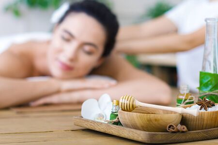Closeup salver with bottles of aroma oil, bowls of salt, honey, healing spices. Young woman is getting thai massage, therapy. Girl is lying on couch in spa ayurveda salon. Relax and health care.