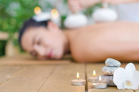 Closeup burning candles, flower, special stones. Young woman is getting thai massage, therapy by herbal bags. Brunette girl is lying on couch in spa ayurveda salon. Relax and health care concept.