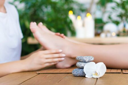 Woman is getting foot massage, therapy. Closeup female hands of master are massaging kneading feet of client. Girl is lying on couch in spa ayurveda salon. Relax and health care concept. Stock Photo